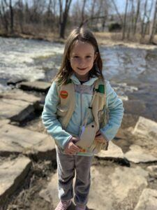 Young girl is standing by river to convey the importance of priorities during social distancing